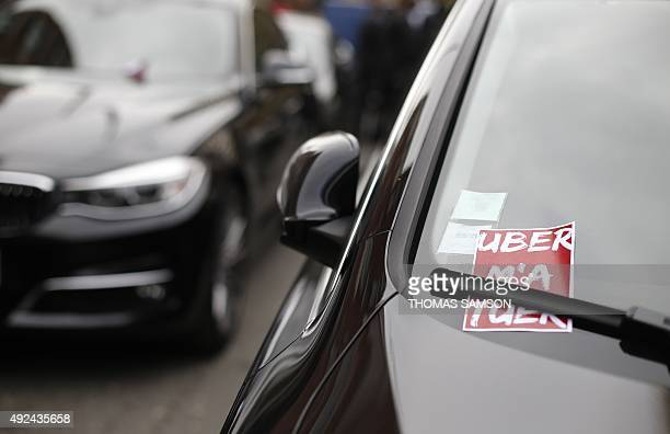 A sticker reading 'Uber kills me' is seen on the windscreen of a car of a driver working for car service company Uber known as VTC drivers in France...