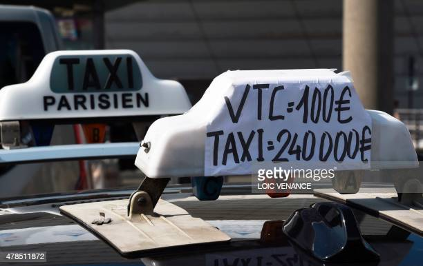 A sticker reading 'VTC 100 euros Taxi 240 000 euros' refering to the amount a cab driver in France has to pay for his licence opposed to the VTC...