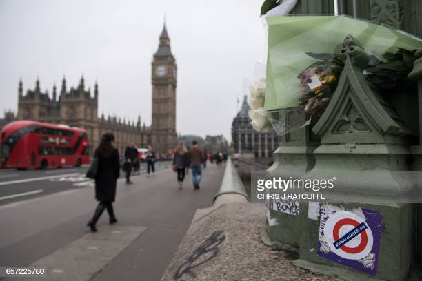A sticker reading '#WeAreNotAfraid' is stuck on a parapet next to floral tributes on Westminster Bridge leading to the Houses of Parliament in...