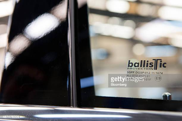 A sticker with the Ballistic Protection Co logo is affixed to the windshield of a car after work was completed at the company's armored car workshop...