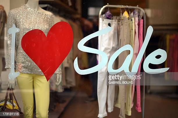 Stickers read ''I love sale' in a shop window during the summer sales on July 8 2013 in Rome AFP PHOTO / GABRIEL BOUYS