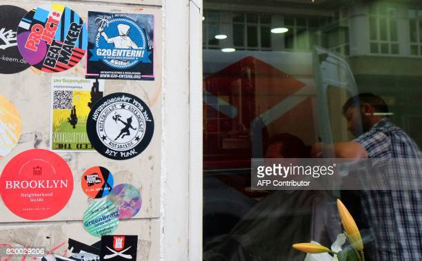 Stickers which adress the G20 summit are pictured on the wall of a hairdresser shop in Hamburg northern Germany on July 202017 / AFP PHOTO / PATRIK...