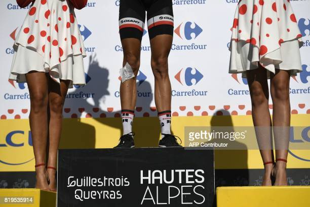 A sticking plaster is seen on a leg of France's Warren Barguil celebrating his polka dot jersey of best climber on the podium at the end of the 1795...
