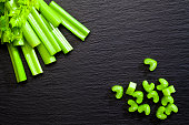 Top view of celery sticks and chopped celery on dark slate background with copy space. DSRL studio photo taken with Canon EOS 5D Mk II and Canon EF100mm f/2.8L Macro IS USM Lens