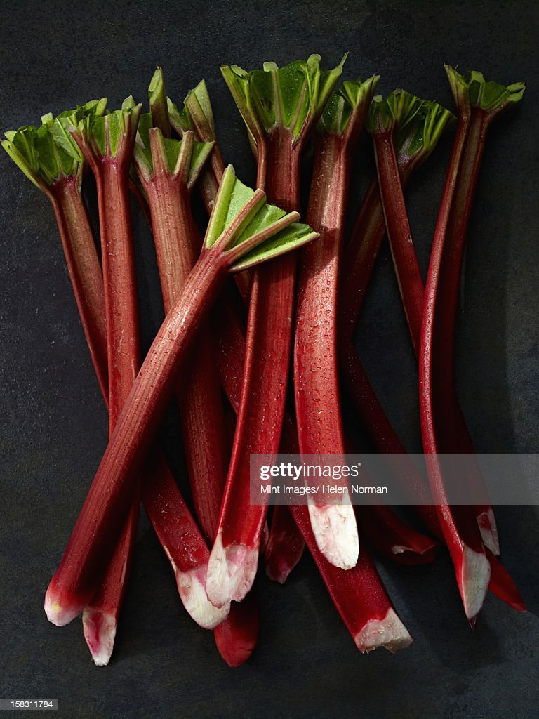 Sticks of fresh rhubarb with long pink stems, and cut leaves.