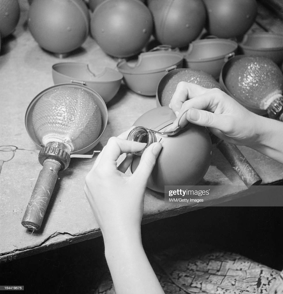 The Production Of The No 74 Grenade In Britain A closeup view showing the protective casing being clipped into place around the glass flask of a...