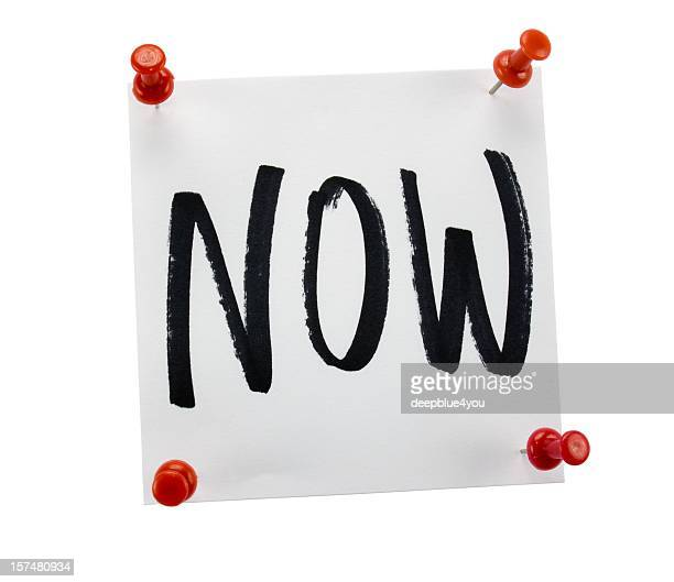 Sticky note with the word NOW on white background