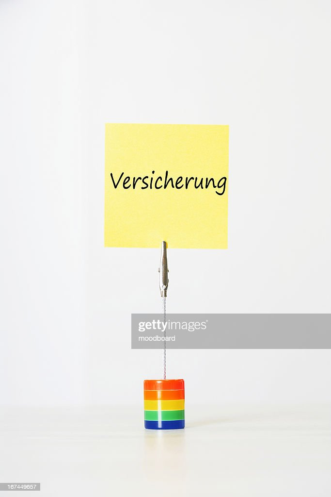 Sticky notepaper with German text ''Versicherung'' (Insurance) clipped to a multicolored card holder : Stock Photo