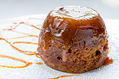 Sticky toffee pudding close up on a white sugar dusted plate drizzled with caramel sauce