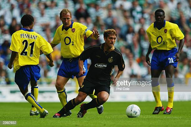 Stilian Petrov of Celtic takes the ball past Jermaine Pennant Ray Parlour and Kolo Toure of Arsenal during the PreSeason Friendly match between...