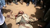 A still from a video shows the body of an MNLA Tuareg rebel lying on the ground and surrounded by civilians in the streets of Gao on June 27 2012...