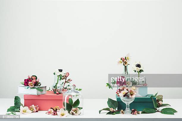 Still life arrangement of flowers and vases spring rose background