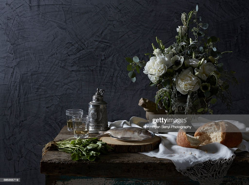 Still life Dutch masters theme with white wine, watercress, bread and fish