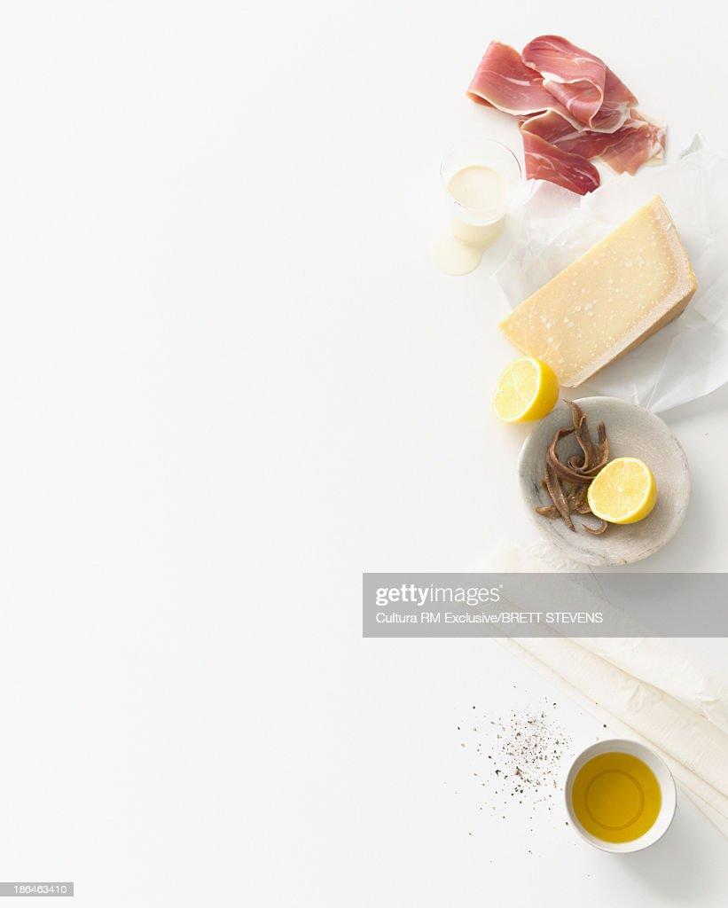 Still life food selection of parma ham, parmesan and anchovies : Stock Photo