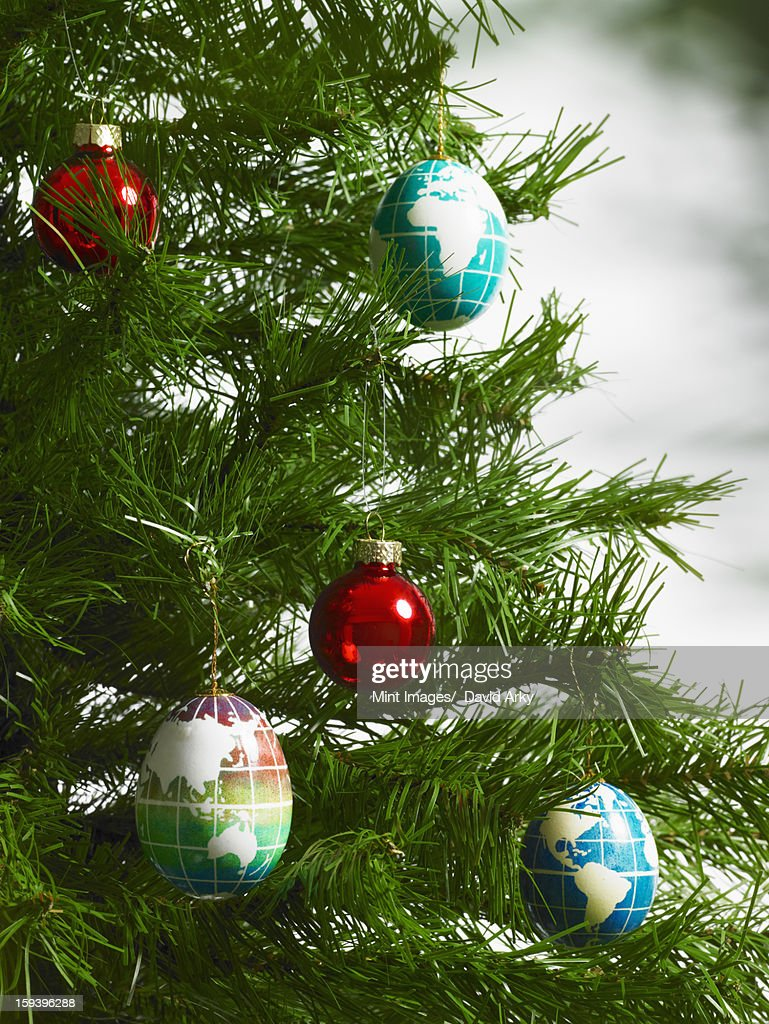 Still life. Green leaf foliage and decorations. A pine tree branch with green needles. Christmas decorations. A small group of red and blue tree ornaments. Oblong shapes with continents outlined on a blue background. : Stock Photo