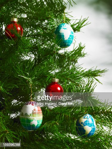 Still life. Green leaf foliage and decorations. A pine tree branch with green needles. Christmas decorations. A small group of red and blue tree ornaments. Oblong shapes with continents outlined on a blue background. : Foto de stock