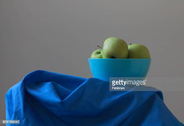 Still life of a blue bowl with yellow apples with window light