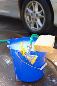 Still life of a bucket of soapy water, a sponge and a hose ready to clean the nearby car.
