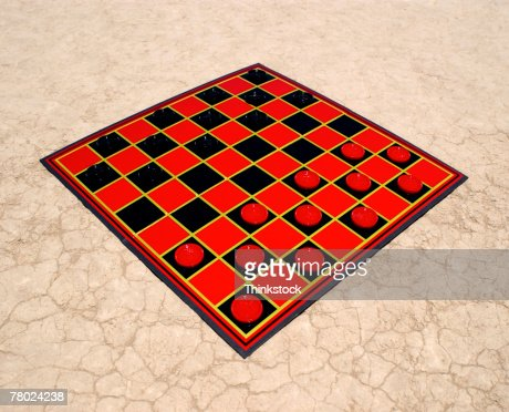 Still life of a game of checkers sitting in the desert.