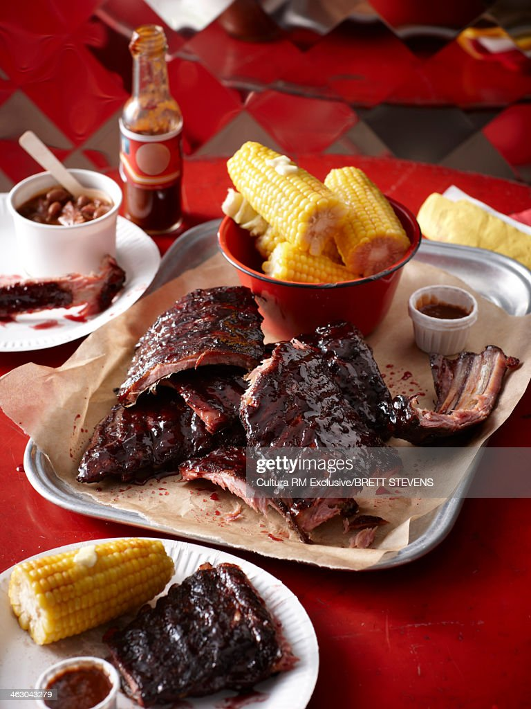 Still life of apple, cherry smoked pork ribs with corn on the cob : Stock Photo