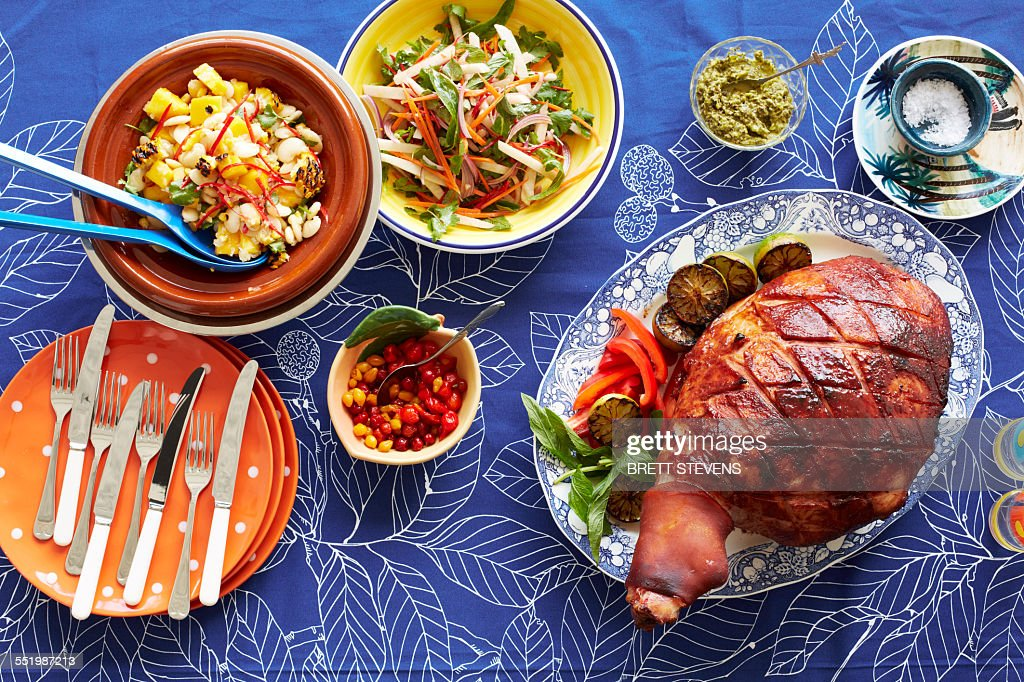 Still life of baked creole ham and side dishes