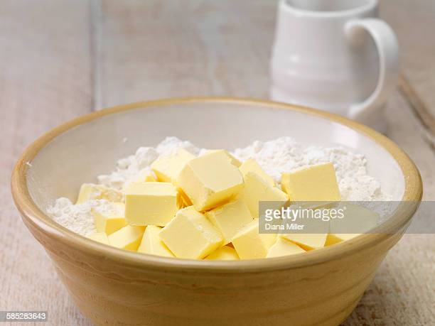 Still life of baking ingredients. Butter cubes and flour in mixing bow