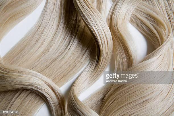 Still life of blond wavy hair on white background.