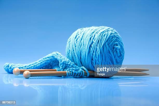 Still life of blue yarn and knitting needles