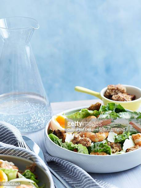 Still life of caesar salad with prawns and croutons
