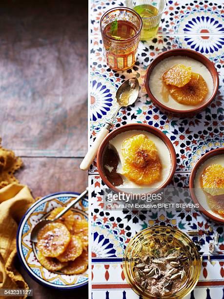 Still life of cardamom custard and caramelized oranges