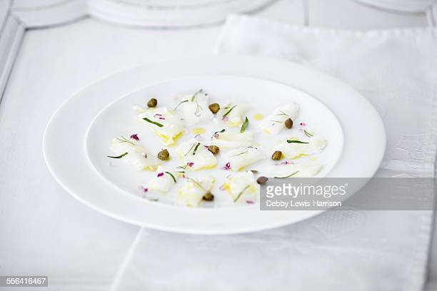 Still life of carpaccio of raw fish, capers and herbs