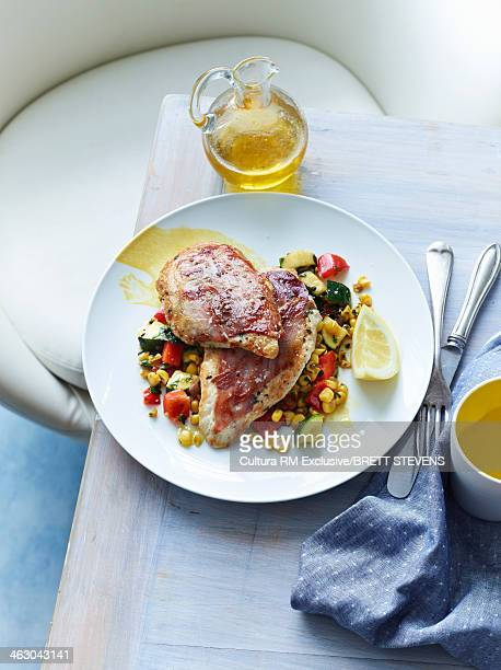 Still life of chicken saltimbocca with vegetables and olive oil