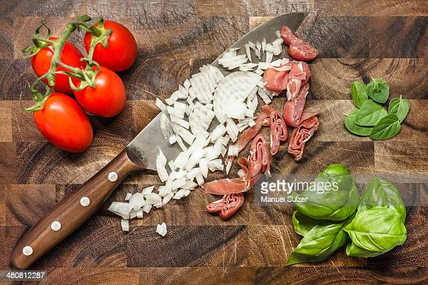 Still life of chopped onion and ham with tomatoes and herbs