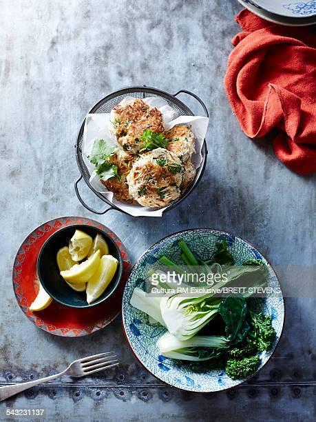 Still life of coconut fish cakes with broccoli and pak choi