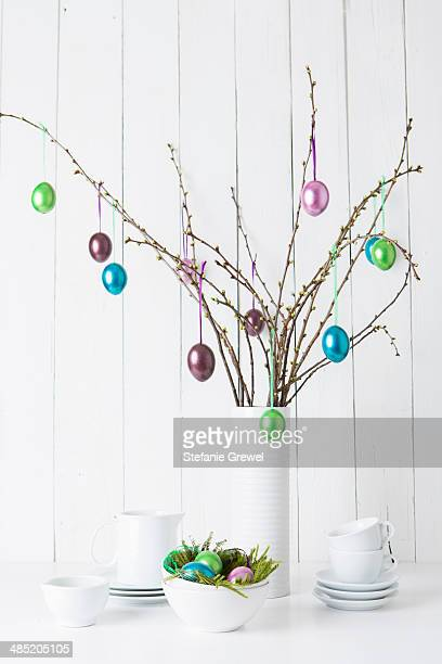 Still life of crockery and shiny easter eggs hanging from twigs