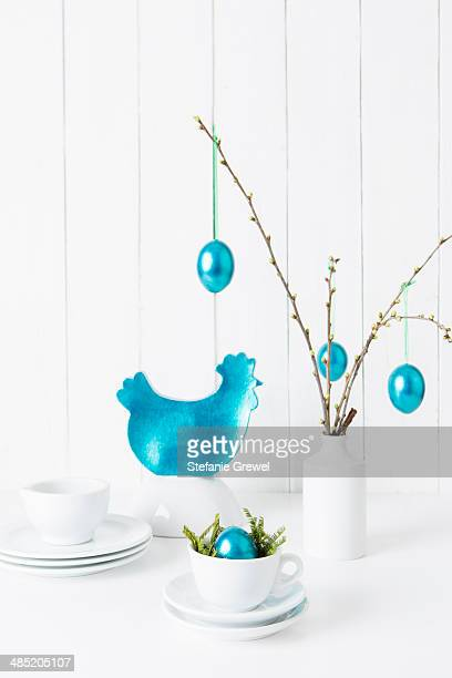 Still life of crockery and turquoise easter eggs hanging from twigs