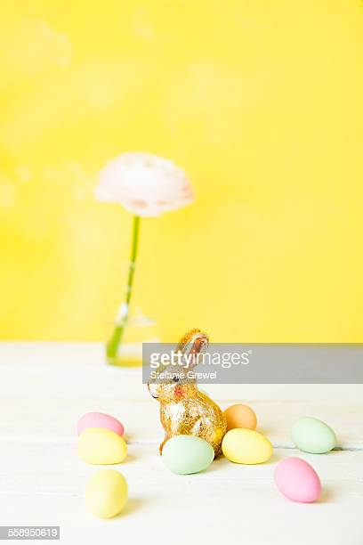 Still life of cut flower in bottle, Easter eggs and bunny