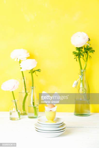 Still life of cut flowers in bottles and Easter egg with bunny ears
