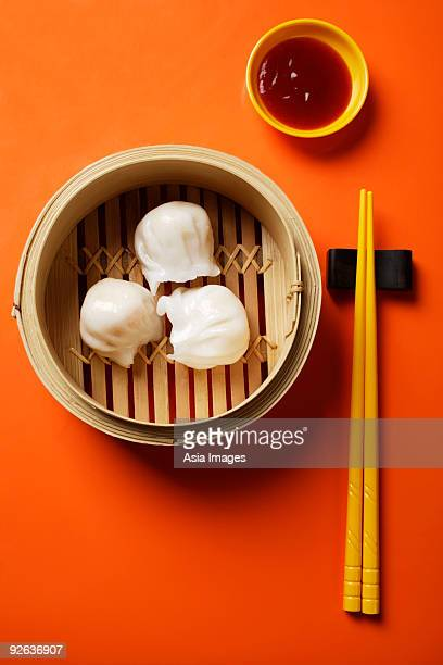 still life of dim sum in bamboo steamer with chopsticks