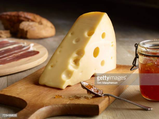 Still life of Edam cheese with quince chutney, on chopping board
