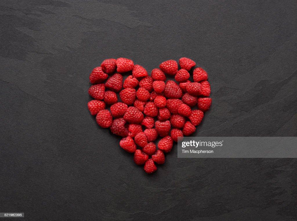 Still life of fresh raspberries arranged in heart shape