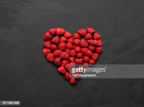 Still life of fresh raspberries arranged in heart shape