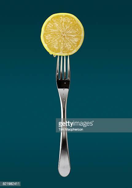 Still life of fresh slice of lemon on fork