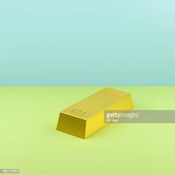 Still life of gold bar on green and blue background