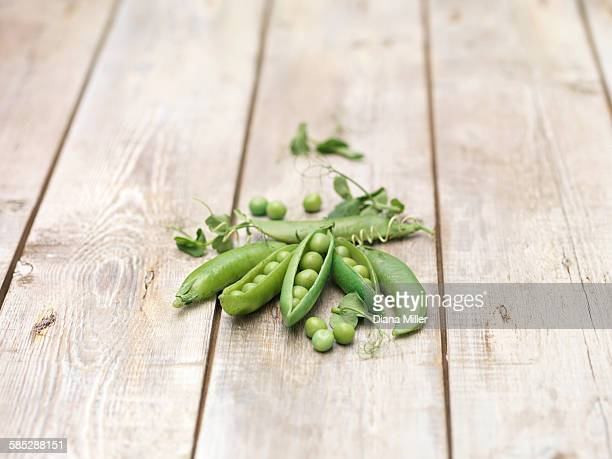 Still life of green peas in pods with pea shoots on wooden table