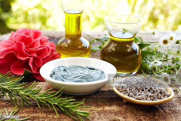 Stillleben von Kräutern, Ölen, eine Schlammmaske, Rosmarin, Blumen