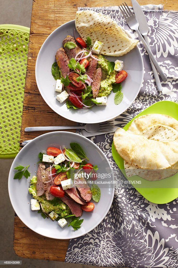 Still life of lamb with pea hummus and pita bread : Stock Photo