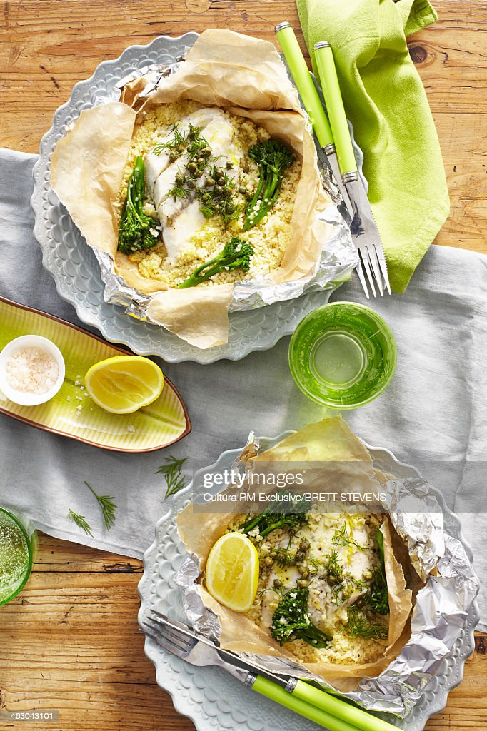 Still life of lemon herb baked fish with couscous : Stock Photo