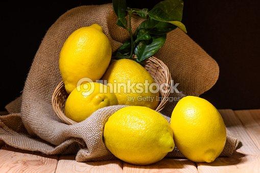 木材、黄麻布や籐のバスケットに葉の緑とレモンのある静物 : ストックフォト
