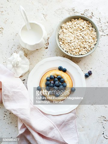 Still life of porridge oats, sponge and blueberries